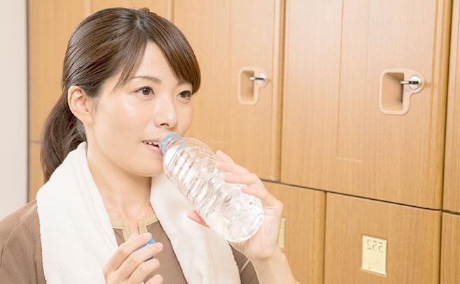 スパの着替え室で水を飲む女性