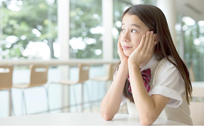 頬杖をついて外を見てる女子中学生