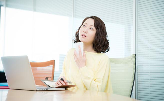 スマホでSNSをしながら考えてる女性