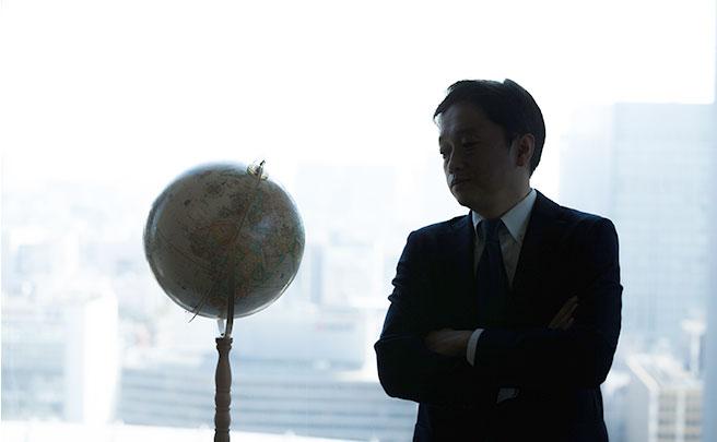 地球儀を見つめる男の人