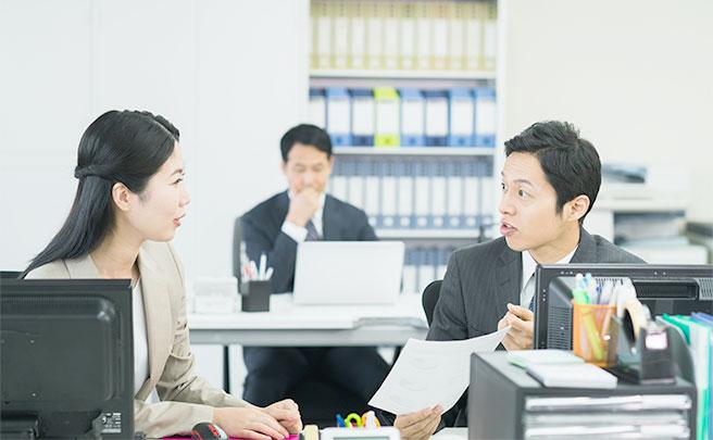隣に座っている女性から仕事を頼まれている男性