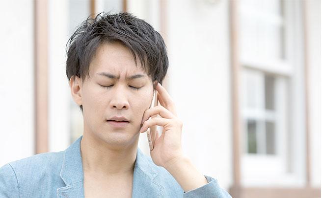 辛い表情をして電話する男性