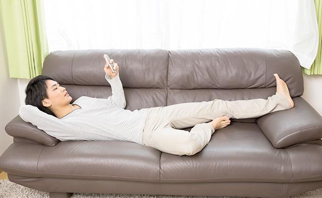 ソファで電話を見る男性