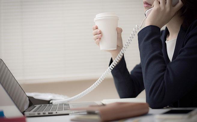 残業でコーヒーを持ちながら電話に出る女性社員