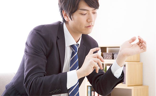 香水をつける男性