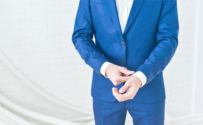 青いスーツを着る男性
