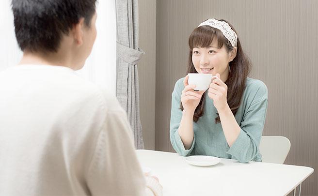 カップを持て男性の話を聞く女性