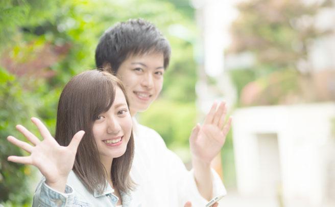 笑顔で手を振る男女