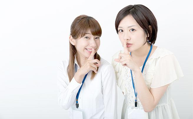 唇に立てた人差し指をあてて内緒であることをアピールしてる女子社員