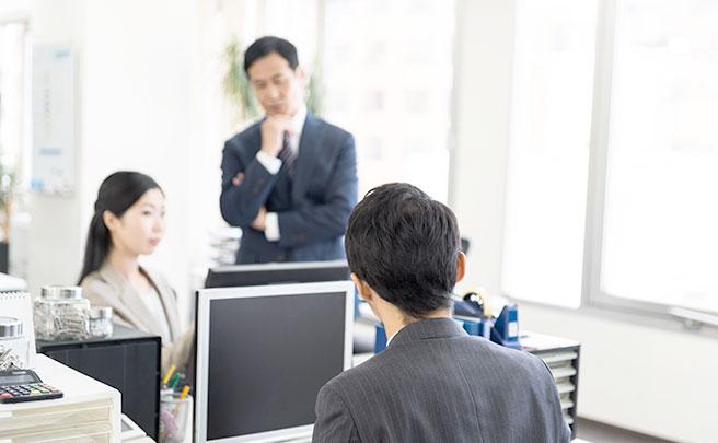 パソコンの前に座る男性と上司の様子