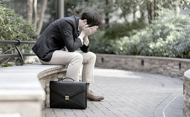 顔を隠して泣く男性