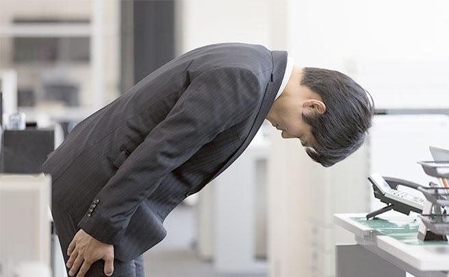 頭を下げて謝罪しているスーツを着た男性