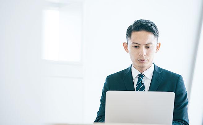 パソコンで真面目に仕事を行う男性