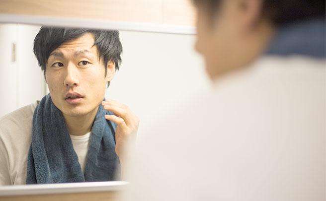 鏡で自分の顔を見てる男性
