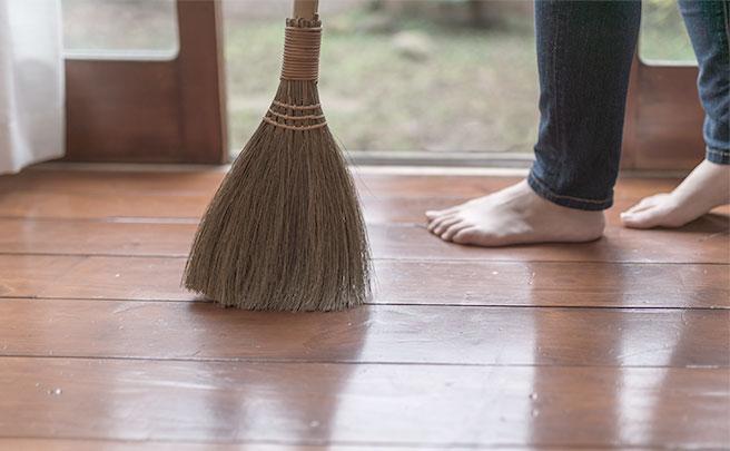 掃除をする女性の脚とほうき