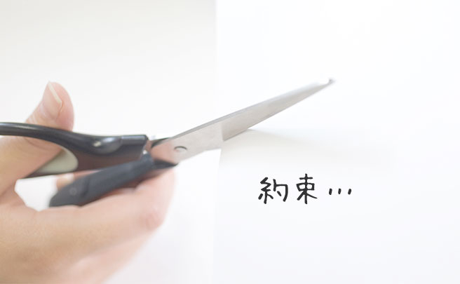 ハサミで紙を切っている人