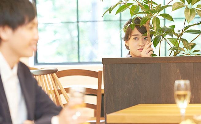 隣の席で食事する男性を影から見てる女性