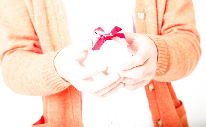 小さいプレゼントの箱を持った男性の手