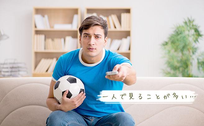 一人でサッカーを見る男性