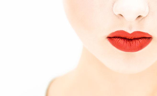 真っ赤なリップをつけた女性の唇