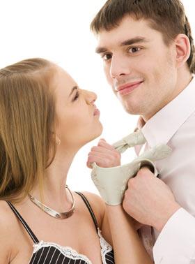 男の首にまかれたネクタイを掴んで浮気について問い詰めてる女性