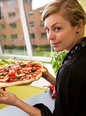 手作りピザを差し出す女性