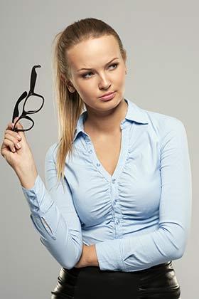 眼鏡を片手に睨む女性