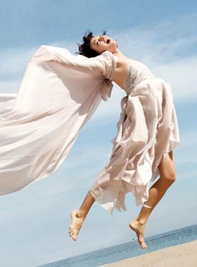 砂浜ではっちゃけてジャンプしてる女性