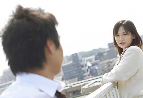 屋上で話をしてる男女