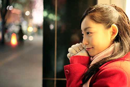 明るい赤いコートで彼氏を待つ彼女