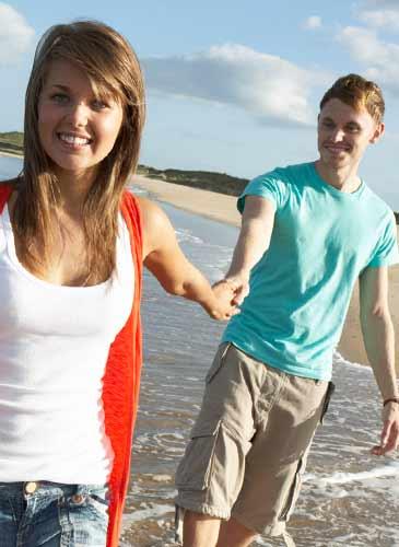 手をつないで砂浜を歩くカップル