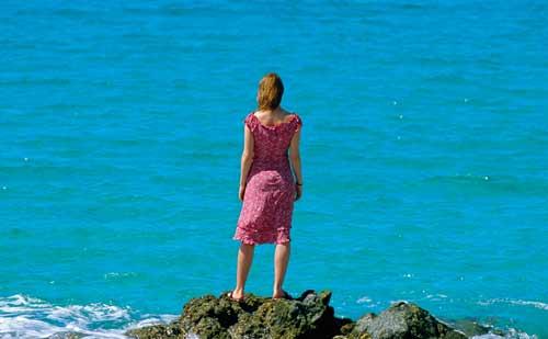 海で遠くを見つめる女性