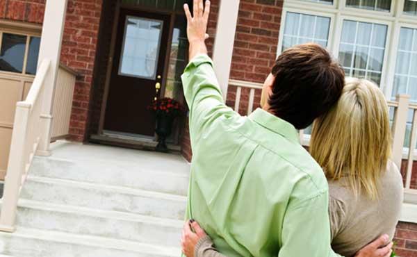 家の前で手を振るカップル