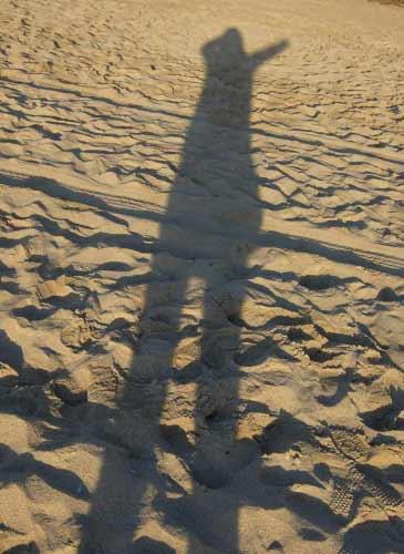 砂浜で伸びる女性の影