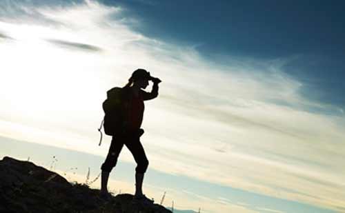 バックパックを背負い山から待ちの風景を眺める女性