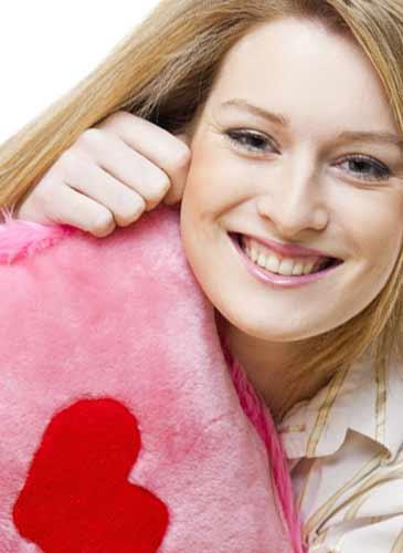 ハートのクッションを抱えて微笑む女性