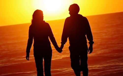 夕日に向かって手をつなぐカップル
