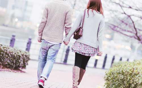 二人手をつないで歩くカップル