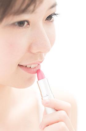 ピンクのリップを塗る女性