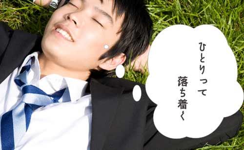 草原で1人の時間を満喫しながら昼寝するサラリーマン