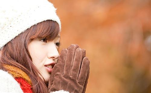 手を口元で温める女性