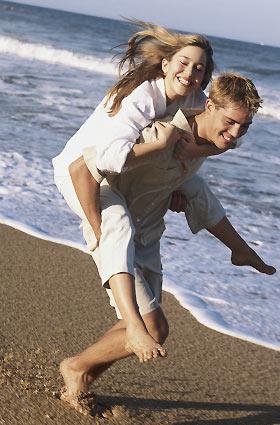 砂浜で恋人をおんぶする男性